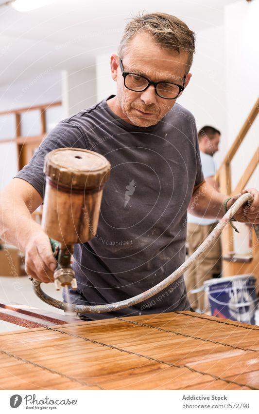 Handwerker, der in einer Schreinerei mit Airbrush Lack auf eine Holzjalousie aufträgt Kunsthandwerker Spray lackieren Mann Lamellen Firnis Holzarbeiten Jalousie