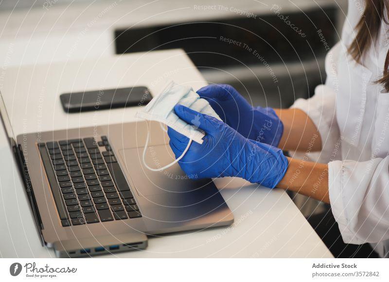 Frau mit Schutzmaske und Handschuhen am Laptop Coronavirus Mundschutz heimwärts Arbeit behüten benutzend abgelegen Arbeitsplatz Apparatur Gerät Sicherheit COVID