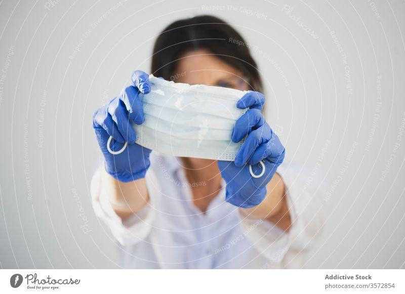 Anonyme Frau mit Schutzmaske und Handschuhen zu Hause Coronavirus Mundschutz behüten zeigen COVID Sicherheit Pandemie Risiko Krankheit ernst Ausbruch