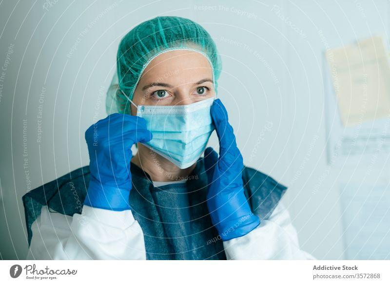 Ärztin mit Schutzmaske und Schutzbrille Mundschutz medizinisch behüten Coronavirus COVID Frau Krankenpfleger Arzt Sicherheit Sanitäter anhaben angezogen Uniform