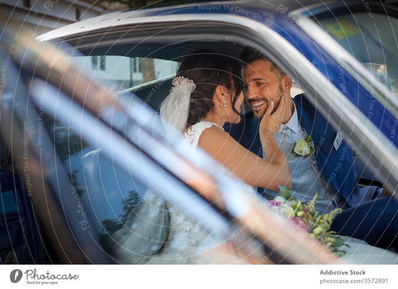 Erfreutes frisch vermähltes Paar in Luxuswagen Jungvermählter PKW Braut striegeln Brautkleid Hochzeit Reichtum stilvoll Anzug Glück Freude Lächeln heiter Inhalt