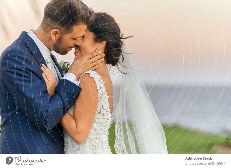 Neuvermähltes Paar umarmt sich am Meeresufer während eines atemberaubenden Sonnenuntergangs Jungvermählter striegeln Braut tropisch Reichtum Hochzeit Umarmung