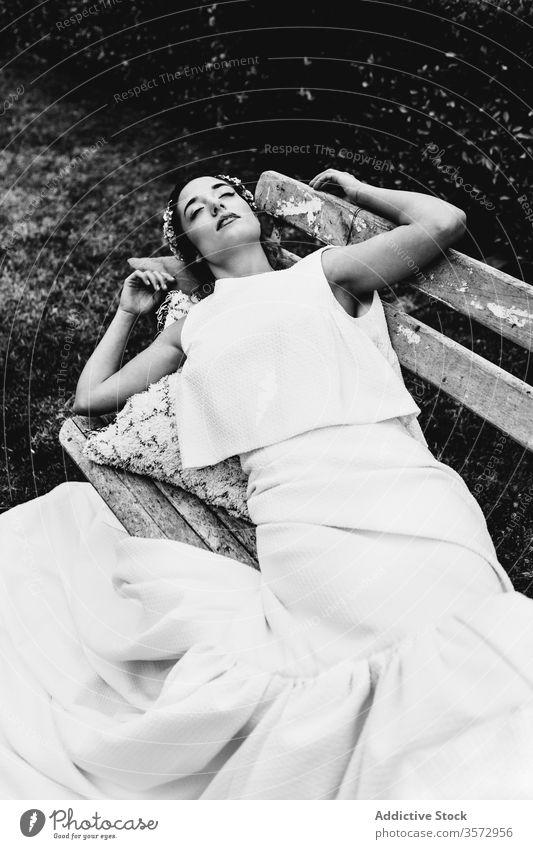 Junge Braut schläft auf Bank Frau schlafen Park Hochzeit elegant Konzept Festakt ruhen jung Kleid Lügen sich[Akk] entspannen ruhig Gelassenheit idyllisch Stil