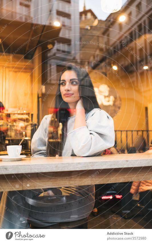 Fröhliche junge Frau sitzt im Cafe Café heiter trendy Stil genießen Kaffee Fenster Abfertigungsschalter trinken gemütlich Kantine sich[Akk] entspannen Glück