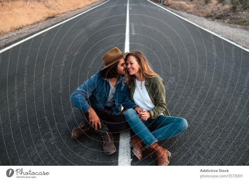 Glückliches Paar sitzt auf der Strasse und berührt sich an den Nasen Lächeln Berührungsnase Straße Termin & Datum Liebe Landschaft reisen Angebot Zusammensein