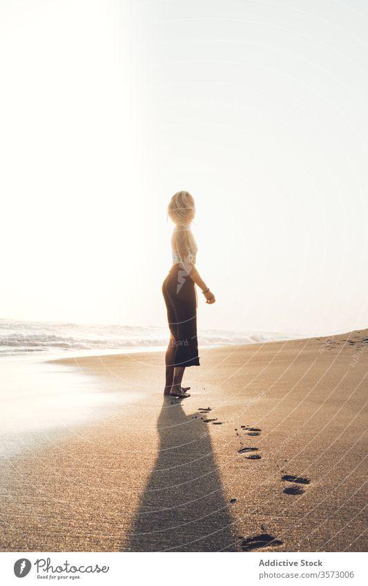 Schlankes junges Weibchen am feuchten Sandstrand stehend Frau Meereslandschaft Harmonie Einsamkeit Frieden winken Hipster nass MEER allein Küste Windstille