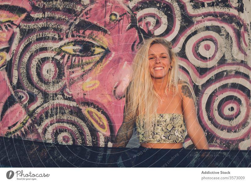 Fröhliche junge Dame steht nahe der Mauer mit bunten Graffiti auf der Straße Frau Streetstyle Freiheit Glück Sommer Wand Lächeln Kunst heiter urban Stil Tattoo
