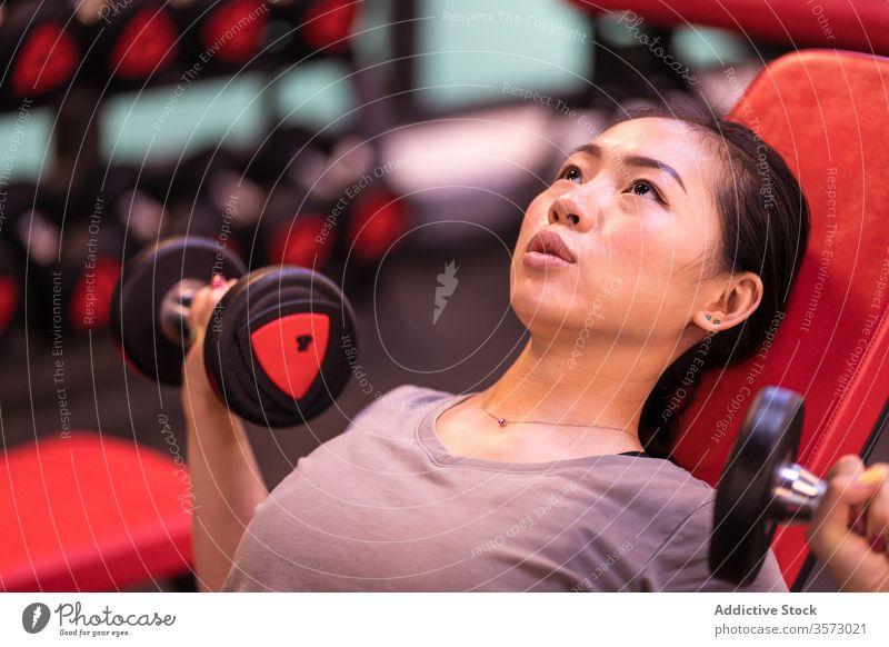 Starke ethnische Sportlerin trainiert mit Hanteln auf Bank in moderner Turnhalle Frau Fitness Kurzhantel Presse Truhe Training Steigung Übung Athlet