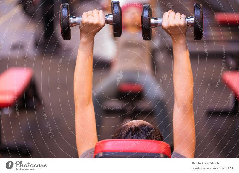 Anonyme starke ethnische Sportlerin trainiert mit Hanteln auf der Bank in moderner Turnhalle Frau Fitness Kurzhantel Presse Truhe Arme hoch Training Steigung