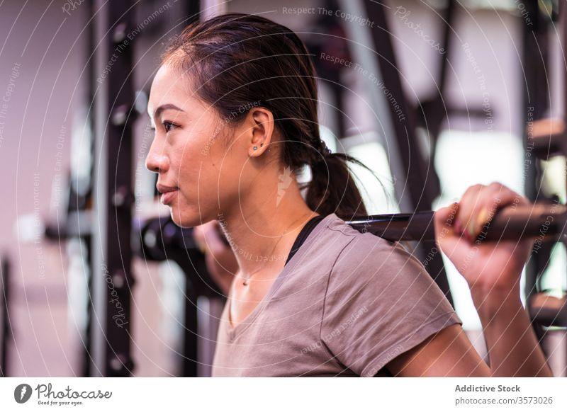 Kräftige junge asiatische Sportlerin macht Kniebeuge mit Langhantel in moderner Turnhalle Frau Curl-Hantel Training aktive Kleidung Maschine Gerät Fokus atmen