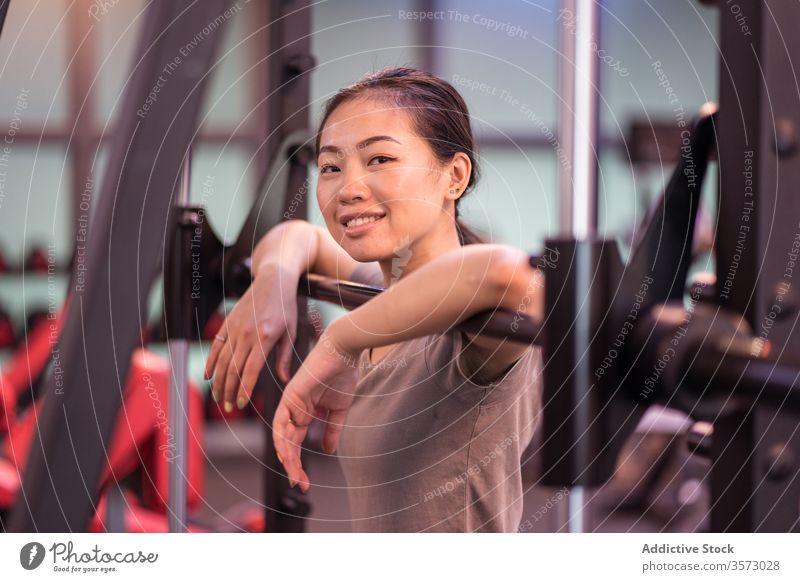 Positive asiatische Sportlerin lehnt sich in moderner Turnhalle an Langhantel und schaut in die Kamera Frau Curl-Hantel ruhen Training Fitnessstudio Maschine