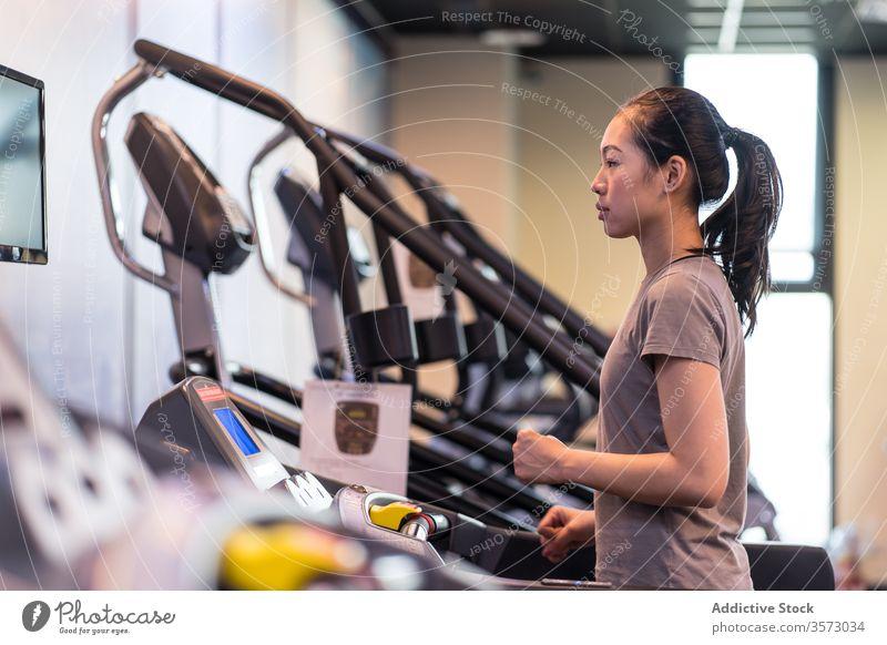 Junge ethnische Sportlerin läuft auf dem Laufband, während sie in einem modernen Fitnessstudio trainiert Frau laufen Herz Übung Athlet Training Gesundheit