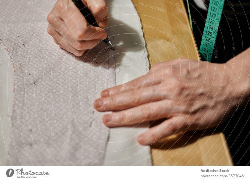 Unerkennbare Meisterarbeit beim Übertragen von Mustern auf Stoff in der Werkstatt Frau Gewebe nähen Grundriss transferieren Designer Näherin Schere hölzern