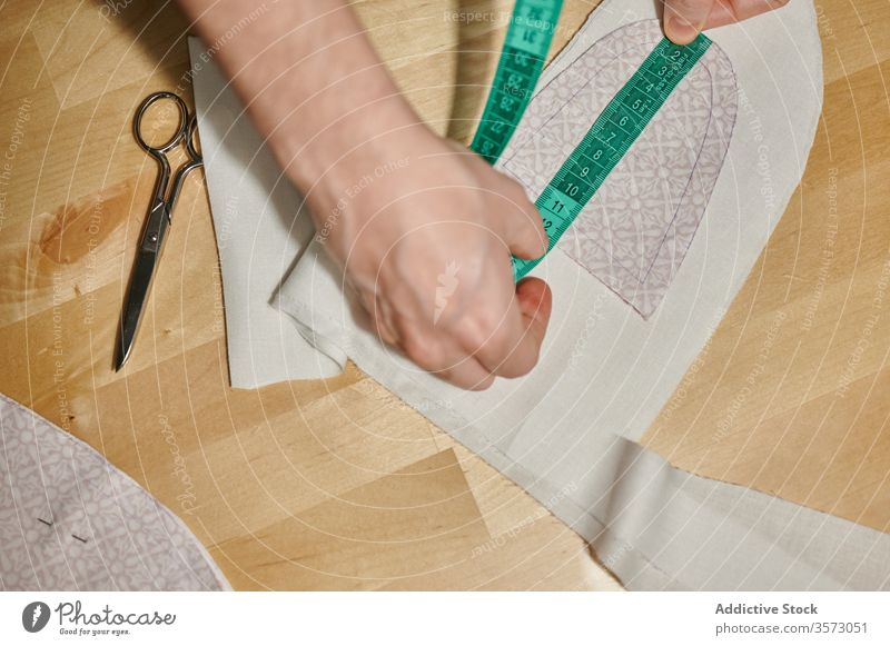 Nicht erkennbarer Designer misst Textildetails mit Klebeband Spielfigur Gewebe messen Material Muster Detailaufnahme nähen Schere hölzern Tisch heimwärts Stoff
