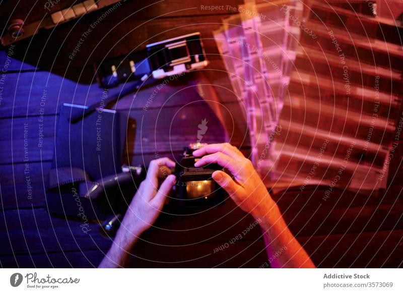Anonymer Fotograf, der mit Film und Retro-Fotokamera im Studio arbeitet Filmmaterial Tisch altehrwürdig Süchtige Konzept Hingabe Leidenschaft professionell