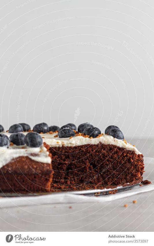 Ein Stück frischer Schokoladenkuchen mit Blaubeeren und Sahne dekoriert auf dem Küchentisch Spielfigur Kuchen gepeitscht Scheibe Schwamm Biskuit weiß
