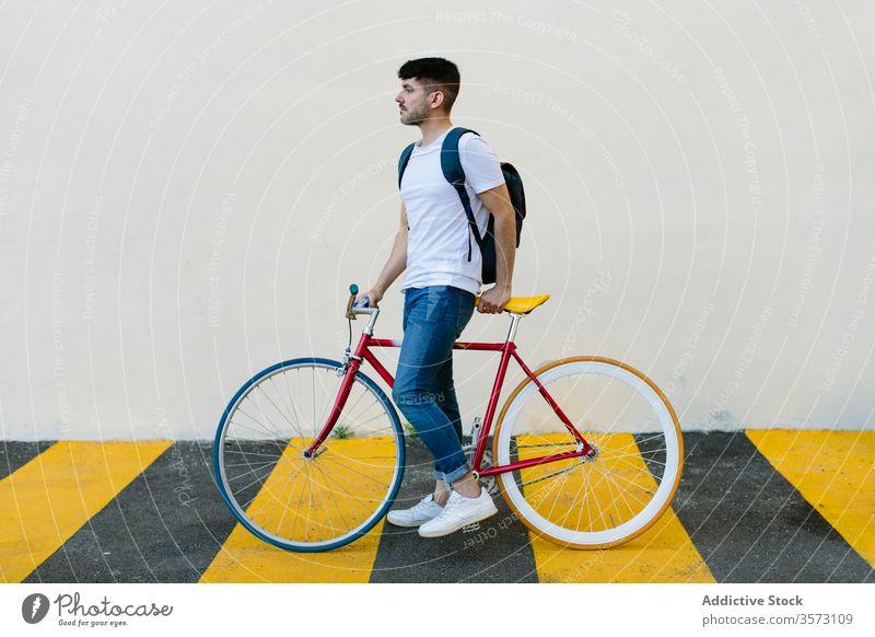 Kaukasischer Mann auf einem Fixie Fahrrad Zyklus urban Rad feststehend Sport Transport Ausrüstung Lifestyle Wand Straße Hipster Mitfahrgelegenheit Pedal
