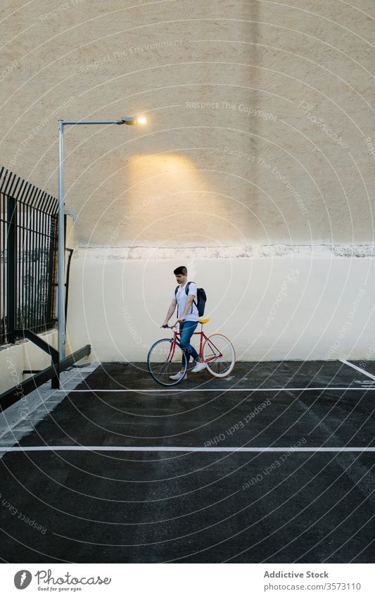 Mann auf dem Fahrrad auf einem Parkplatz Fixie Zyklus urban Rad feststehend Sport Transport Ausrüstung Lifestyle Wand Straße Hipster Mitfahrgelegenheit Pedal