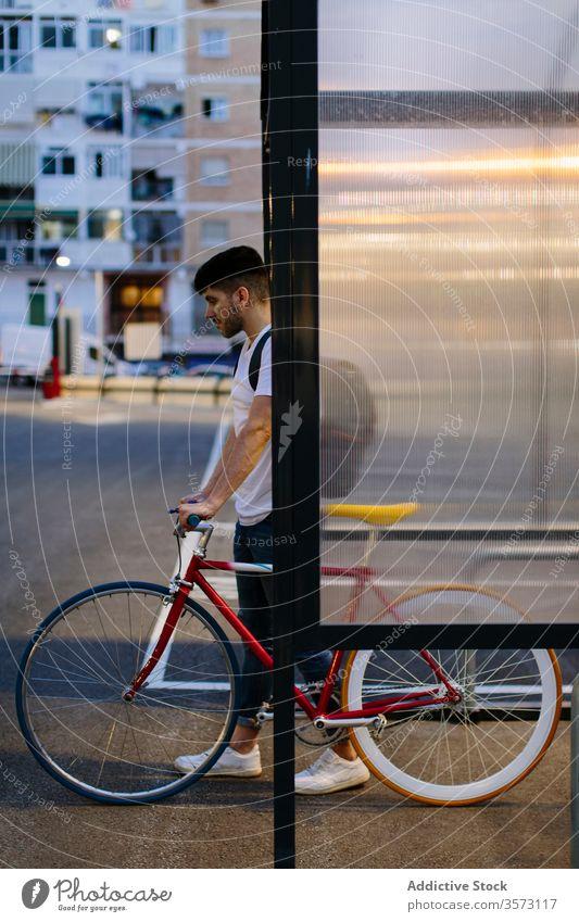 Mann steigt mit einem Fahrrad aus einem Parkplatz aus Fixie Zyklus urban Rad feststehend Sport Transport Ausrüstung Lifestyle Wand Straße Hipster