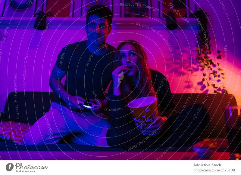 Paar, das auf dem Sofa eine Spielunterlage spielt und Popcorn isst Gamepad Popkorn Nacht Spaß spät spielen Zusammensein genießen unterhalten heimwärts schlaflos