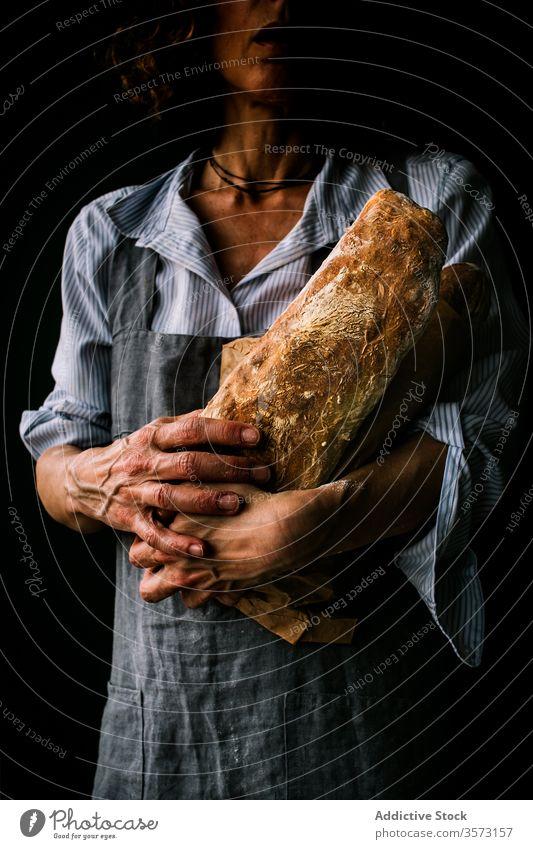 Anonyme Frau mit Ciabattabrot in der Hand Person Halt Mehl Frühstück Schürze Küche Bäcker Bäckerei Teigwaren Kunstgewerbler Verkäufer gebacken frisch Gesundheit
