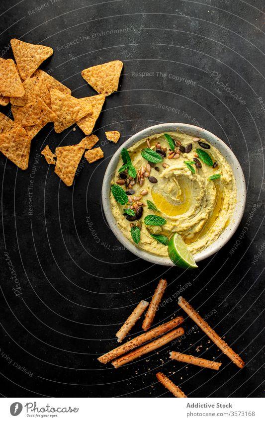 Hummus-Erbsen auf einer Schale in der Nähe von Crackern Antipasti Kichererbsen Erdöl Püree Gesundheit Minze Libanese arabisch eintauchend organisch