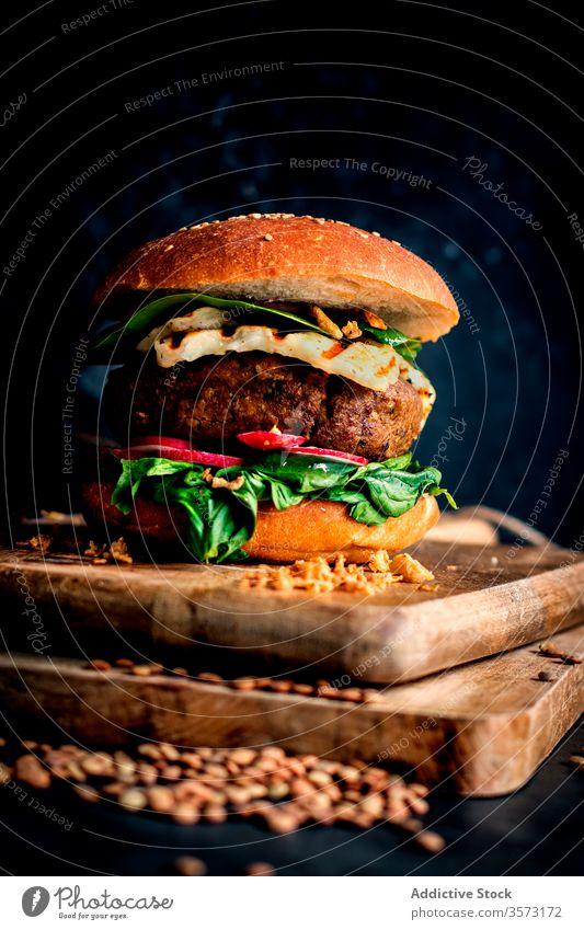 Vegane Linsen-Hamburger auf Holzbrettchen auf dunklem Hintergrund Feinschmecker Linsen-Burger Gemüse-Burger Fastfood Essen gebacken lecker natürlich Lifestyle