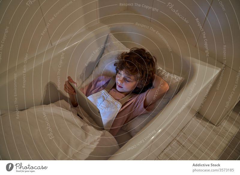 Fröhlicher Junge benutzt Tablette im Badezimmer Karikatur Badewanne Kind gemütlich Kopfkissen Spaß Lügen zuschauen Wochenende benutzend heiter ruhen