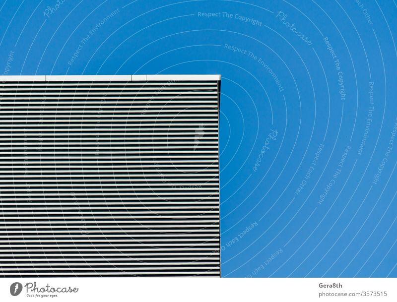 Gestreifte Wand eines grauen, hohen Gebäudes vor einem blauen, klaren Himmel abstrakt abstrakter Hintergrund Winkel Architektur schwarz blanko Sauberkeit
