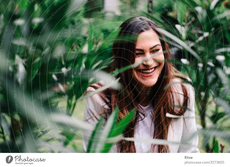 Junge hübsche Frau lacht herzhaft inmitten von grünen Pflanzen draußen im Garten jung lachen lebensfreude Natur Spaß Porträt Glück Fröhlichkeit südländisch