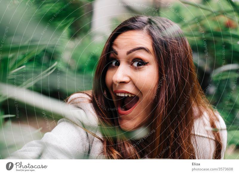 Junge Frau lacht draußen in der Natur freudig euphorisch positiv überrascht in die Kamera Porträt Grimasse jung hübsch erstaunt Quatsch Mädchen Gesicht schön