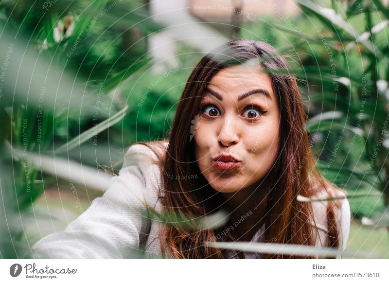 Junge Frau macht eine Duckface Grimasse und guckt überrascht in die Kamera Porträt jung hübsch erstaunt Quatsch Mädchen Gesicht schön Erwachsene attraktiv