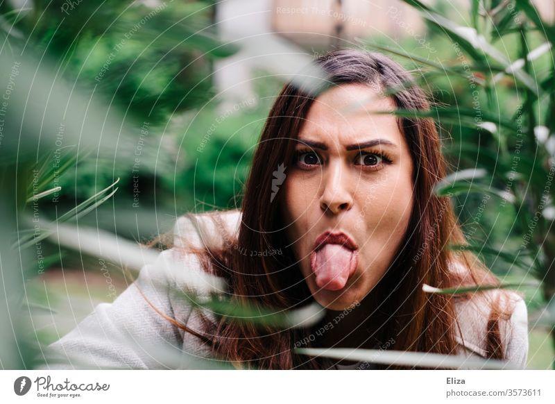 junge Frau guckt böse hinter Pflanzen im Garten hervor und streckt die Zunge raus Zunge rausstrecken frech sauer Erwachsene Mensch 1 Junge Frau genervt Streit