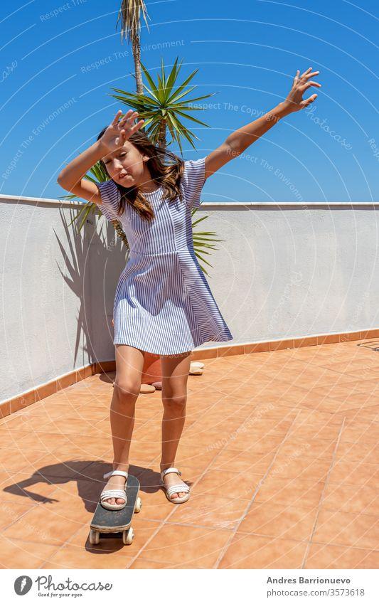 Hübsches kleines Mädchen in einem gestreiften Kleid, das auf der Terrasse ihres Hauses mit einem Skateboard spielt Aussehen Großstadt Glück cool Kleidung Sommer