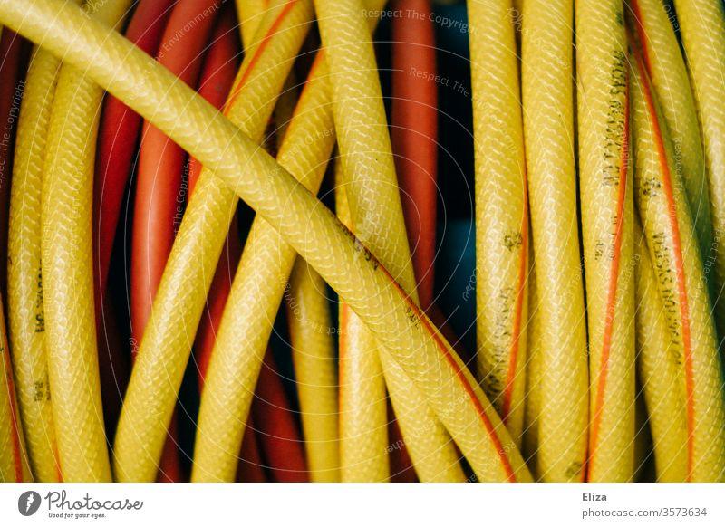 Nahaufnahme eines gelben Gartenschlauchs Wasserschlauch gießen Gartenarbeit Detail aufgerollt Schlauch orange