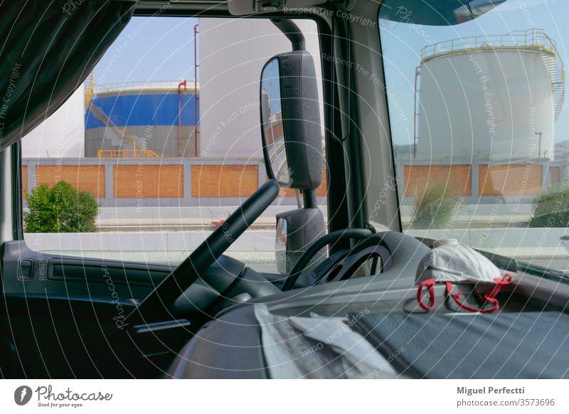 Lkw-Innenraum, Armaturenbrett mit einer Maske und Kraftstofftanks im Hintergrund Lastwagen Kraftstoffe Lager Rückansicht Einlagen Lenkrad Verkehr Mundschutz