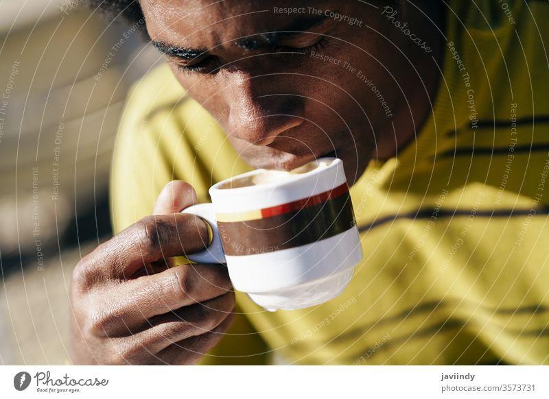 Schwarzer Mann genießt Kaffee im Café, während er im Freien am Tisch sitzt Erwachsener Afrikanisch Afro-Look Amerikaner attraktiv Hintergrund schön Getränk