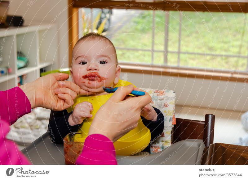 Entzückender kleiner Junge im Fütterungsstuhl, der von seiner Mutter mit einem Löffel gefüttert wird Baby niedlich Europäer Säugling 6 Monate Kaukasier