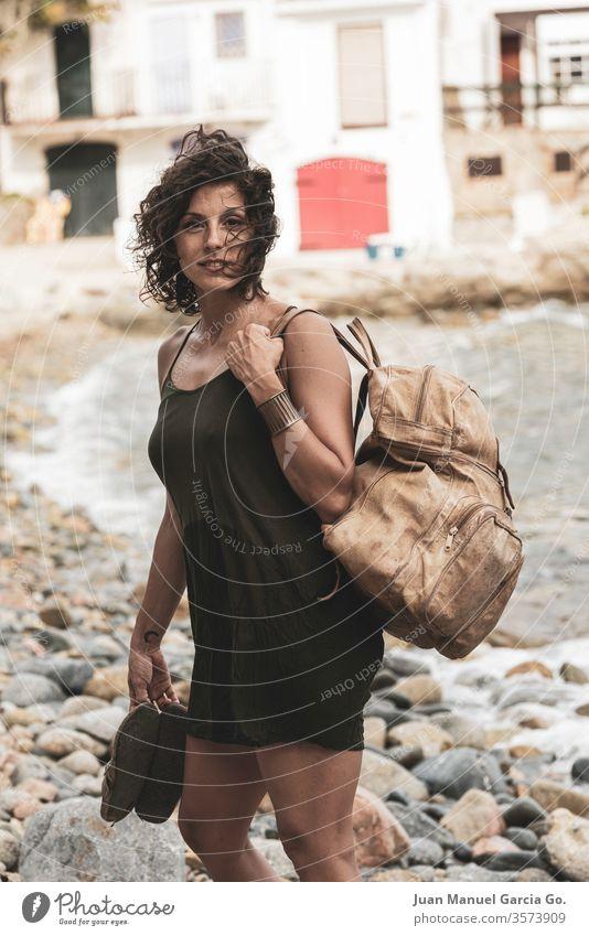Eine schöne weibliche Latina mit einer Tasche und Hausschuhen am Ufer Frau Mädchen Schönheit jung weiß hübsch Menschen attraktiv Erwachsener Lächeln Glück