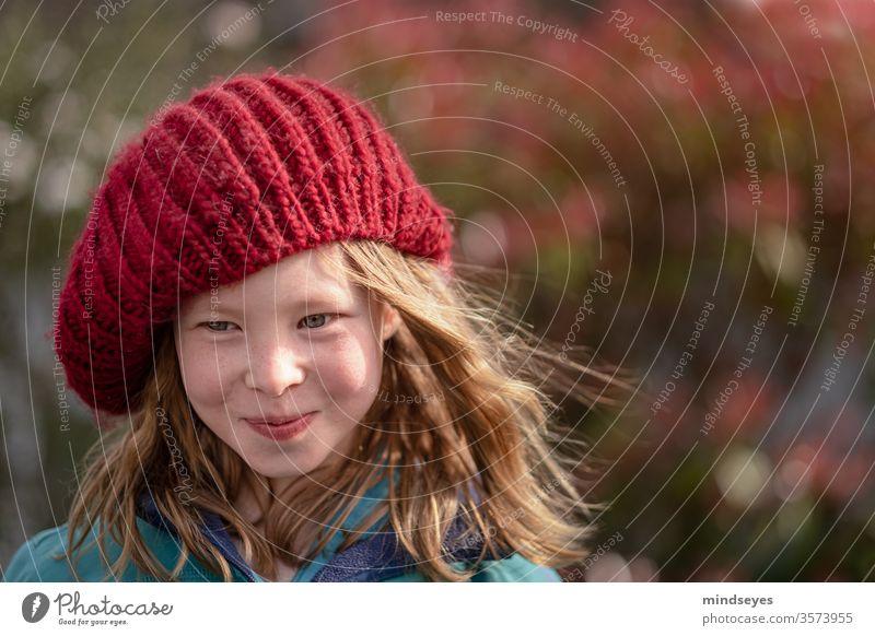 Das Mädchen mit der Mütze portrait winter mütze strickmütze Winter Gesicht lachen Farbfoto Freude lange haare Wind in den Haaren (sofern vorhanden) rot stricken