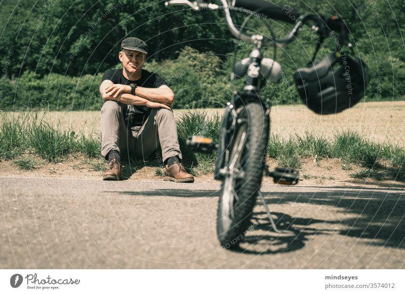 Mann sitzt hinter einem Kinderfahrrad im Gras Fahrrad Fahrradfahren Fahrradhelm Kinderrad sitzen Sport Pause Natur Außenaufnahme Freizeit & Hobby Farbfoto