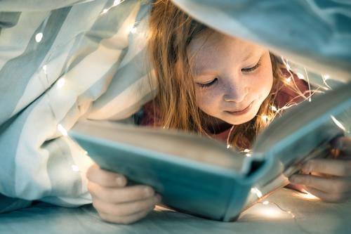 Mädchen liest Buch unter der Decke Kind Portrait lesen buch bett bettdecke lichterkette kindheit heimlich versteckt spannend Farbfoto lernen Innenaufnahme