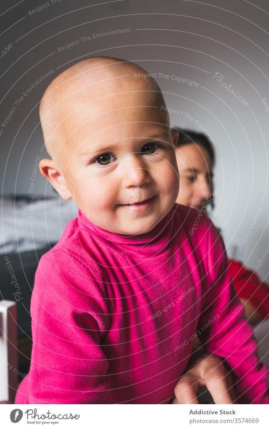 Entzückender kleiner Junge spielt zu Hause mit Spielzeug Spielzimmer heimwärts charmant neugierig Kleinkind lässig rosa Hemd Kind Stock Aktivität spielerisch