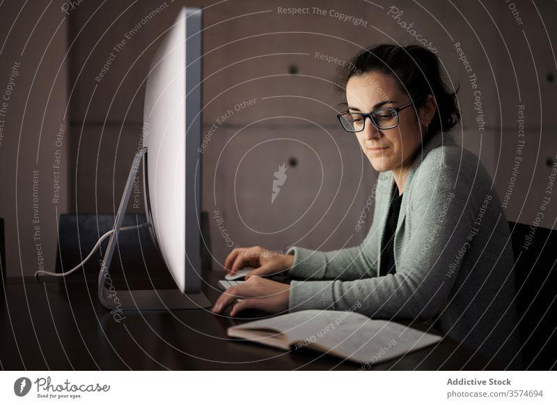 Fokussierte Frau, die zu Hause mit Gadgets arbeitet Arbeit heimwärts Apparatur Smartphone Computer Telearbeit benutzend Browsen jung lässig ernst Konzentration