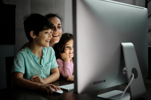 Fröhliche Frau mit Kindern schaut Video am Computer an Mutter benutzend Smartphone Zusammensein Telearbeit Kinderbetreuung Glück heiter heimwärts Kommunizieren