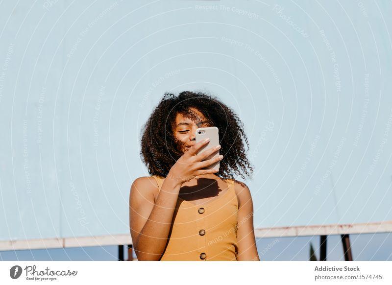 Junge zufriedene ethnische Frau benutzt Handy auf der Straße gegen leere große Tafel in einem Vorort Smartphone Plakatwand verwenden Freude Browsen Surfen lesen