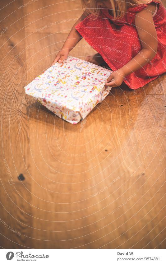 Geburtstag Kind packt ein Geschenk aus Mädchen Geburtstagsgeschenk Geschenke Freude Happy Birthday schenken Boden Parkettboden Holzboden auspacken natürlich