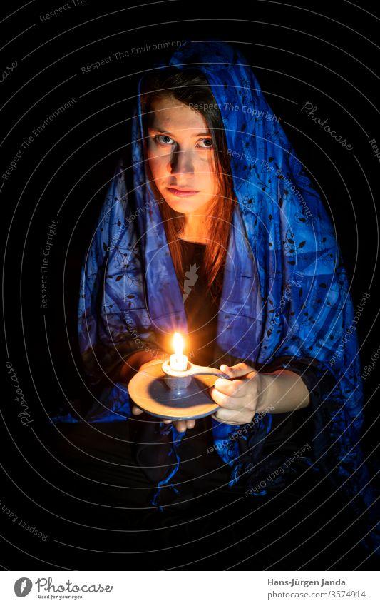 Traurige junge Frau mit Kerze und blauem Kopftuch vor schwarzem Hintergrund Gesicht frau traurig kopftuch portrait frontal profil ernst young kunst düster