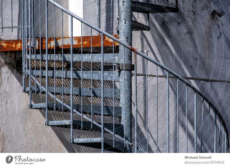 Wendeltreppe außen aus Metall und mit Rost Treppe Architektur Treppengeländer Geländer aufsteigen aufwärts Schatten Menschenleer