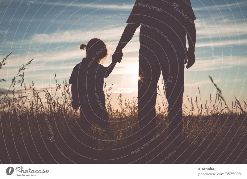 Vater und trauriger Sohn stehen zur Zeit des Sonnenuntergangs im Park. Junge Familie Eltern Pflege Mann Menschen Papa Kind jung deprimiert Trauer unglücklich
